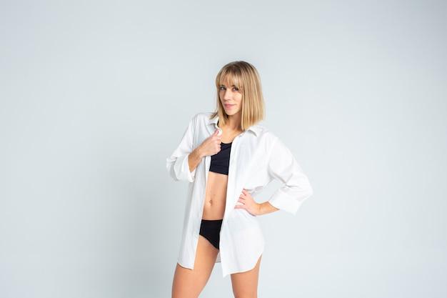 Het mooie slanke blondevrouw stellen in zwarte lingerie en het dragen van een overhemd van witte mannen op een witte achtergrond. copyspace
