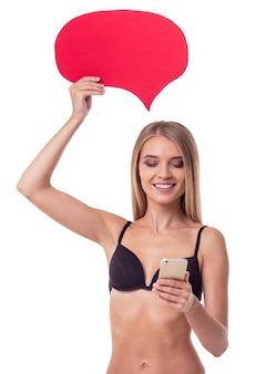 Het mooie slanke meisje in zwarte lingerie gebruikt een smartphone.