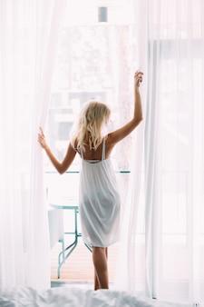 Het mooie slanke meisje met lang haar droeg in witte kleding die zich blootvoets dichtbij het grote venster bevinden. achteraanzicht
