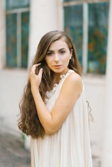 Het mooie slavische meisje met lang golvend haar in beige romantische kleding die haar houden dient haar haar in