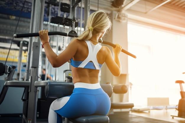 Het mooie sporten jonge vrouw stellen in fitness gymnastiek.