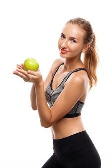 Het mooie sportieve vrouw stellen, die appel houden