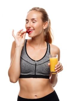 Het mooie sportieve vrouw stellen, glas sap houden en aardbei eten