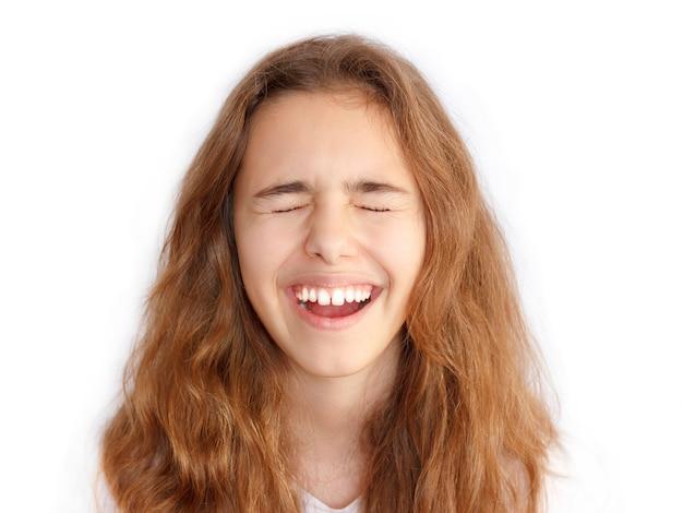 Het mooie tienermeisje met lang haar maakt zeer grappig gezicht en lacht met gesloten ogen