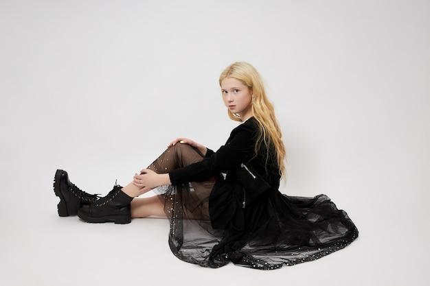Het mooie tienermeisje stellen op de vloer
