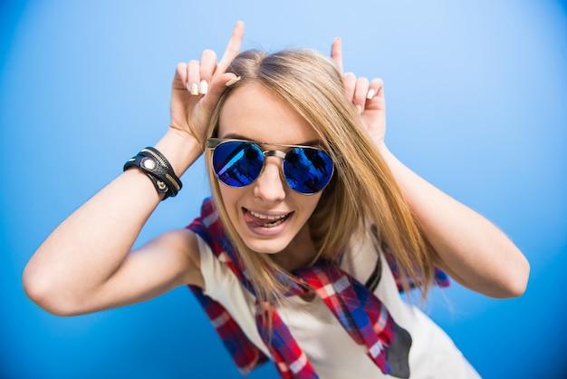 Het mooie trendy blondemeisje stelt