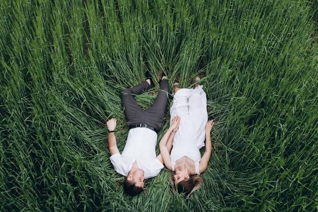 Het mooie verliefde paar ligt op het veld