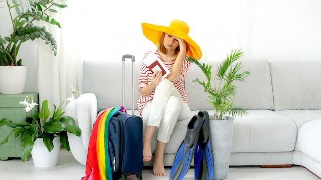 Het mooie verstoorde meisje in een gele hoed blijft thuis en plant een reis op vakantie. wachten op reizen.