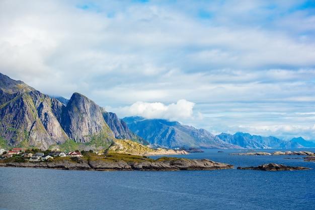 Het mooie vissersdorp aan de fjord. prachtige natuur met bewolkte lucht en rotsachtig strand. lofoten, reine, noorwegen