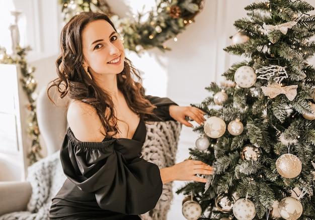 Het mooie vrolijke gelukkige jonge meisje verfraait thuis kerstmisspeelgoed van de nieuwjaarboom