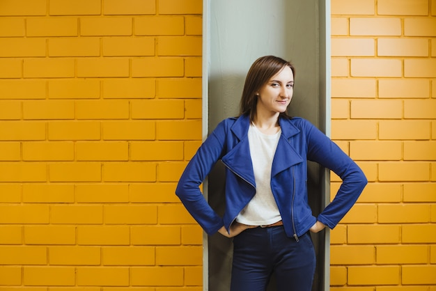 Het mooie vrolijke moderne blondemeisje in zaken stelt tegen een gele bakstenen muur.