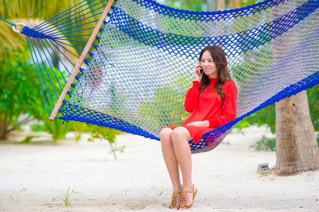 Het mooie vrouw ontspannen bij hangmat op tropisch strand