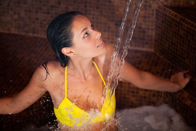 Het mooie vrouw ontspannen onder een waterval ina spa