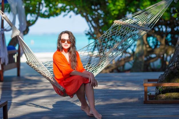 Het mooie vrouw ontspannen op hangmat tijdens de zomervakantie