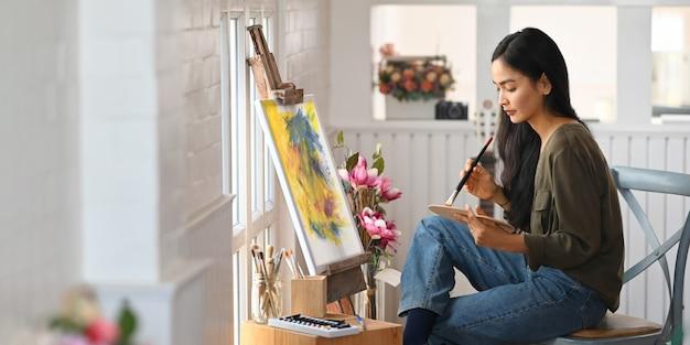 Het mooie vrouw schilderen op canvas met penseel terwijl het zitten bij de stoel