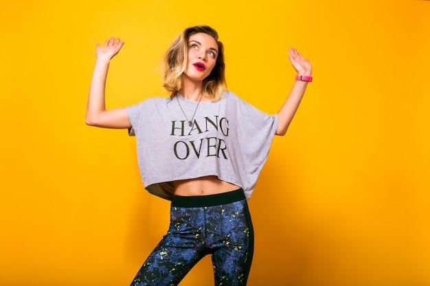 Het mooie vrouw stellen bij studio gele muur, die yogabroek en grappig t-shirt draagt