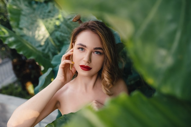 Het mooie vrouw stellen dichtbij groene bladeren
