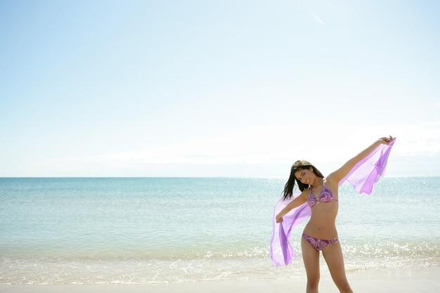 Het mooie vrouw stellen in bikini op het strand