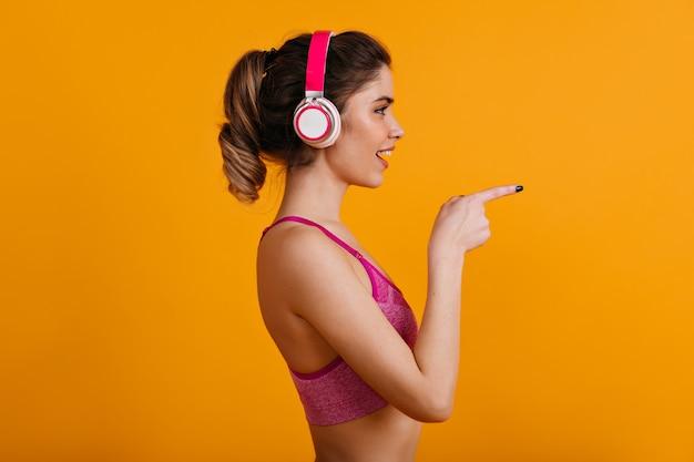 Het mooie vrouw stellen in hoofdtelefoons