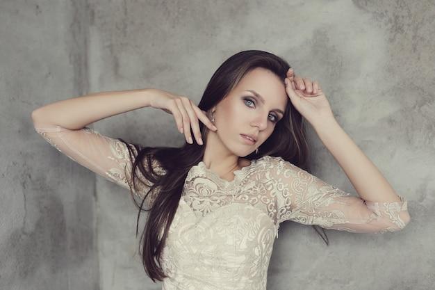 Het mooie vrouw stellen met elegante witte kleding, manierconcept