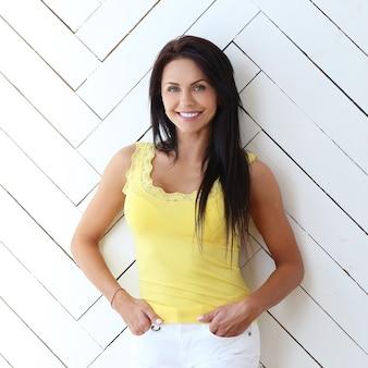 Het mooie vrouw stellen met geel t-shirt