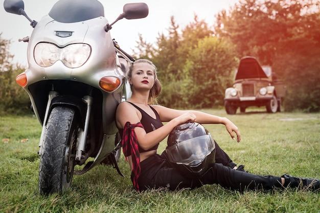 Het mooie vrouw stellen met helm en motorfiets