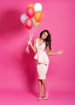 Het mooie vrouw stellen met multi gekleurde ballons
