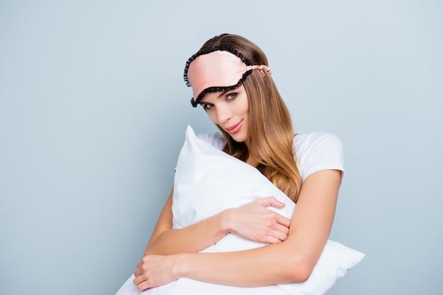 Het mooie vrouw stellen met nachtmasker en hoofdkussen