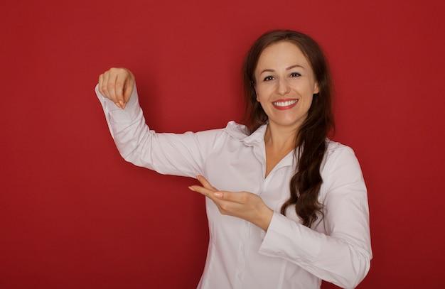 Het mooie vrouw tonen, die iets op de palm van haar hand voorstellen