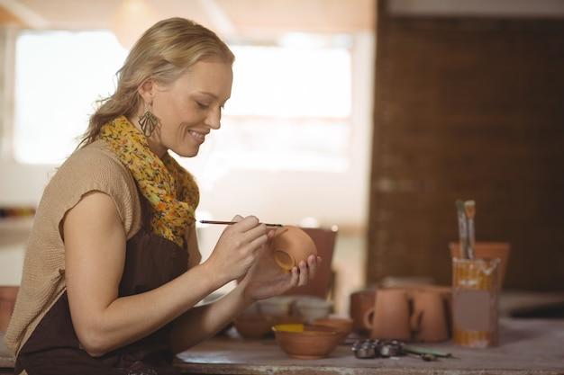 Het mooie vrouwelijke pottenbakker schilderen op kom