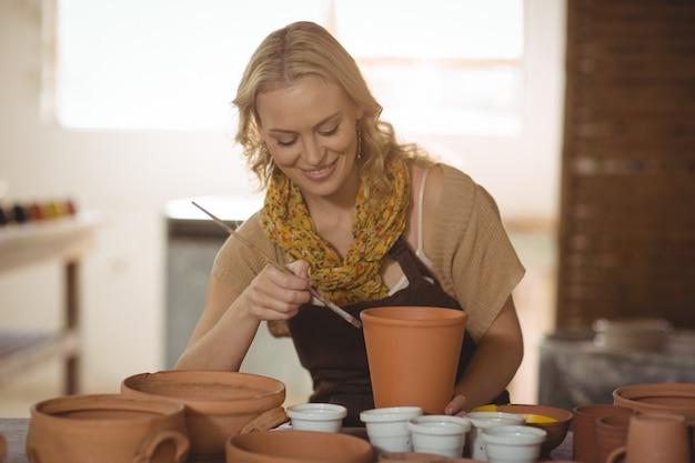 Het mooie vrouwelijke pottenbakker schilderen op pot
