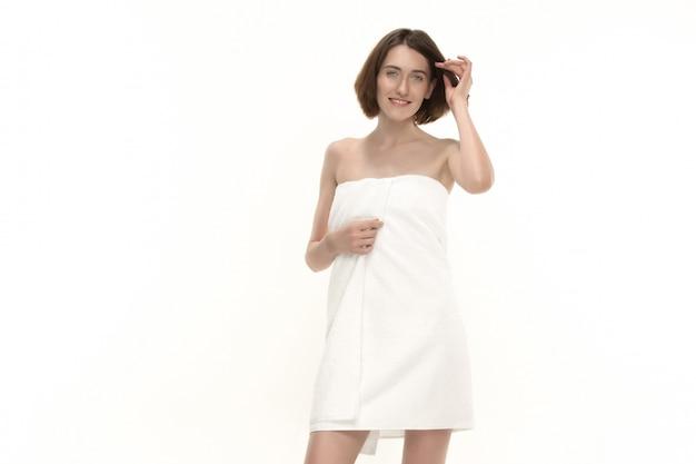 Het mooie vrouwelijke vrouw stellen met handdoek die zijn lichaam behandelt