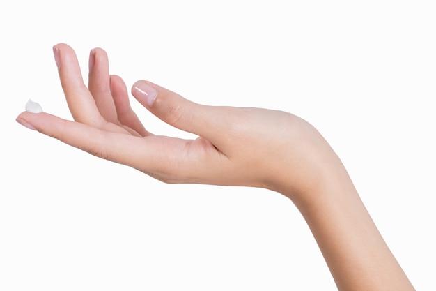 Het mooie vrouwenhand ontspannen met van toepassing die lotion op vingerpunt op witte achtergrond wordt geïsoleerd