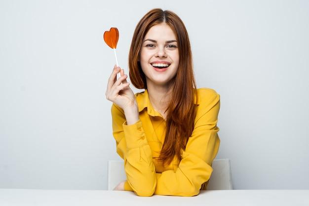 Het mooie vrouwenmodel met een hartlolly aan de lijst in een geel overhemd stelt verschillende emoties. valentijnsdag