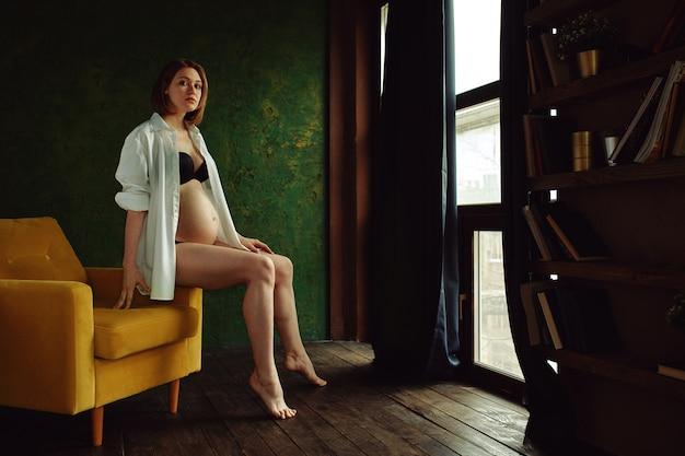 Het mooie zwangere meisje met rood haar zit op een stoel bij het venster. zwangerschap kunst concept. zwanger filmen, een kleurenspel. het begin van een nieuw leven.