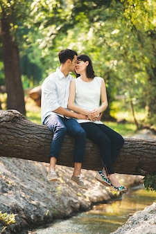 Het mooie zwangere paar ontspannen buiten in het bos