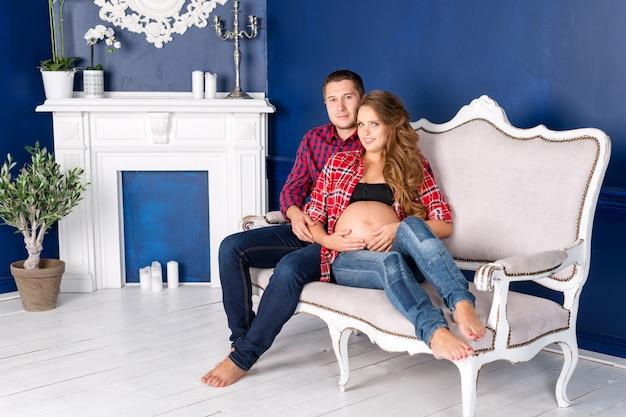 Het mooie zwangere paar ontspannen op bank thuis samen. gelukkige familie, man en vrouw die een kind verwachten.