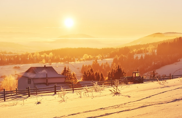 Het mysterieuze winterlandschap bestaat in de winter uit majestueuze bergen. fantastische zonsondergang. huizen opnemen in de sneeuw. foto beleefdheid briefkaart. karpaten