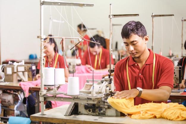 Het naaien van de mens op een sewinghine bij een kledingsfabriek