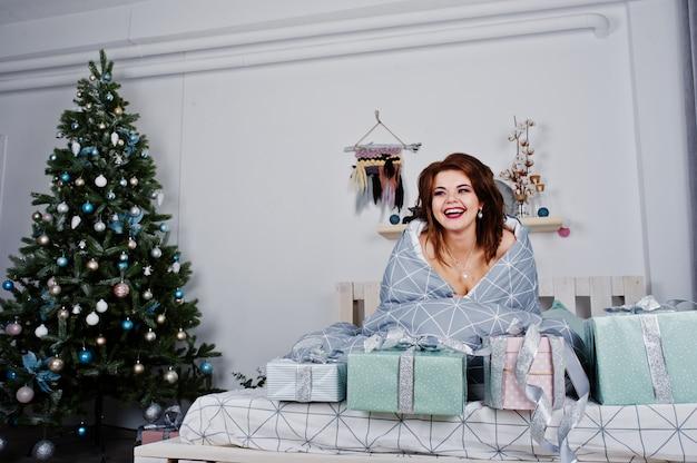 Het naakte meisje liggen op het bed die tegen nieuwe jaarboom behandelen met stelt dozen voor
