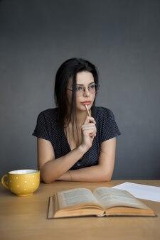 Het nadenken over aantrekkelijke jonge vrouw met in hand pen denken en aantekeningen maken. mooie jonge