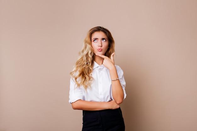 Het nadenkende blonde vrouw stellen isoleert op beige muur. stijlvolle casual werkkleding.