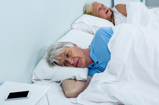 Het nadenkende hogere mens ontspannen op bed met telefoon op lijst