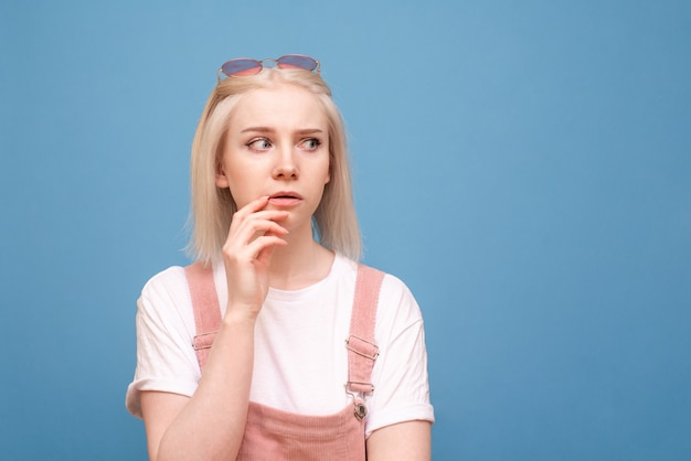 Het nadenkende tienermeisje in leuke kleren kijkt zij aan zij op een blauwe achtergrond, een dicht portret
