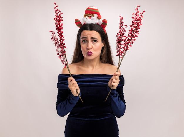Het nastreven van lippen jong mooi meisje die blauwe kleding en de hoepel van het kerstmishaar dragen die lijsterbes tak houden die op witte achtergrond wordt geïsoleerd