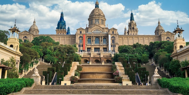 Het nationaal paleis in de tuinen van barcelona, spanje en de mensen ervoor. bewolkte lucht