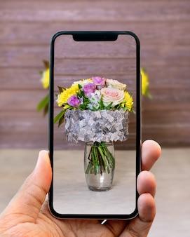 Het nemen van foto van bloemboeket in de vaas met mobiele telefoon