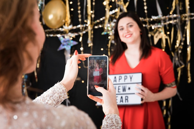Het nemen van foto van meisje dat gelukkig nieuw jaarteken houdt