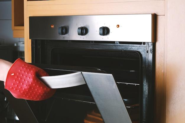Het nemen van gebakken dienblad uit oven met keukenhandschoenen