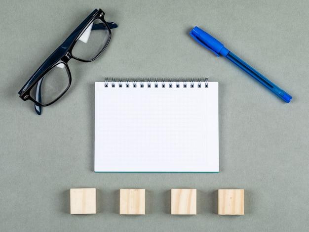 Het nemen van nota'sconcept met notitieboekje, pen, oogglazen, houten elementen op grijze hoogste mening als achtergrond. ruimte voor tekst. horizontaal beeld